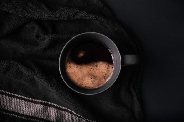 Tasse à café avec mousse yin et yang sur fond noir en vue aérienne