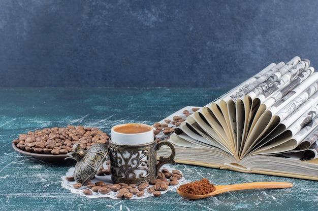 Tasse de café mousseux, assiette de grains de café et livre sur table en marbre.