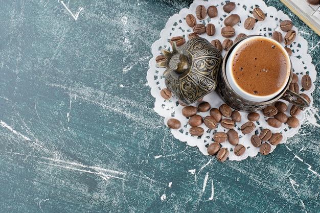 Tasse de café mousseux et grains de café sur une surface en marbre.
