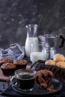 Une tasse de café, des muffins au chocolat, des pains au fromage et du lait.