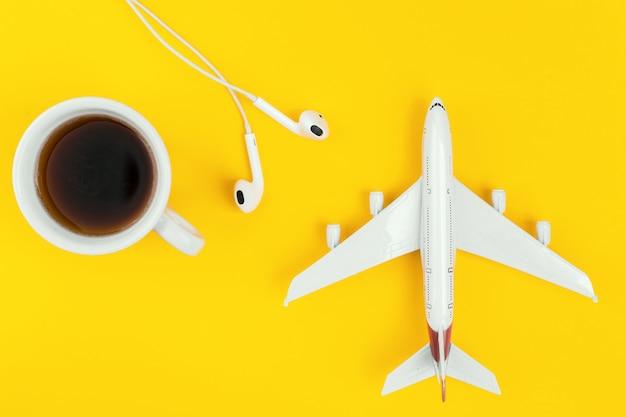 Tasse de café noir, avion et casque sur fond jaune.