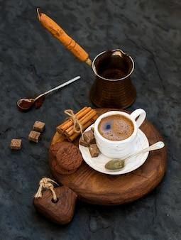 Tasse de café noir avec des biscuits au chocolat, des bâtons de cannelle et des morceaux de sucre de canne sur une planche en bois rustique sur fond de pierre sombre.