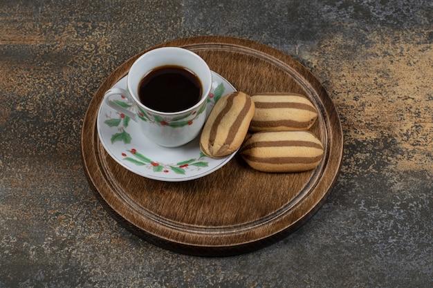 Tasse de café noir avec des biscuits sur une surface en marbre.