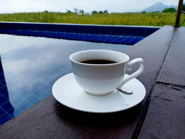 Tasse de café noir chaud bouchent une piscine le matin