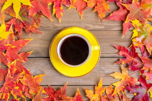 Tasse de café noir chaud sur une table en bois avec des feuilles tombées en automne jaunes, orange et rouges