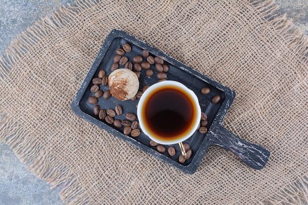 Une tasse de café noir avec cookie sur tableau noir. photo de haute qualité