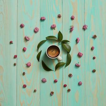 Tasse de café noir dans un cadre rond avec des feuilles et des fleurs, pose à plat
