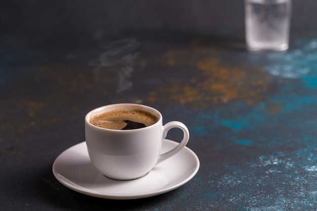 Une tasse de café noir dans une tasse à bord bleu, arrière-plan flou.