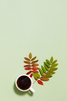 Tasse de café noir et feuilles d'automne jaune rouge sur papier vert pastel
