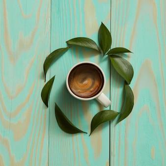Tasse de café noir et feuilles vertes. mise à plat