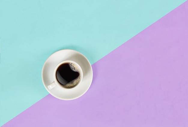 Une tasse de café noir sur fond bleu et lilas vue d'en haut