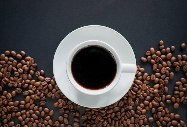Tasse de café noir sur fond noir avec des grains de café torréfiés