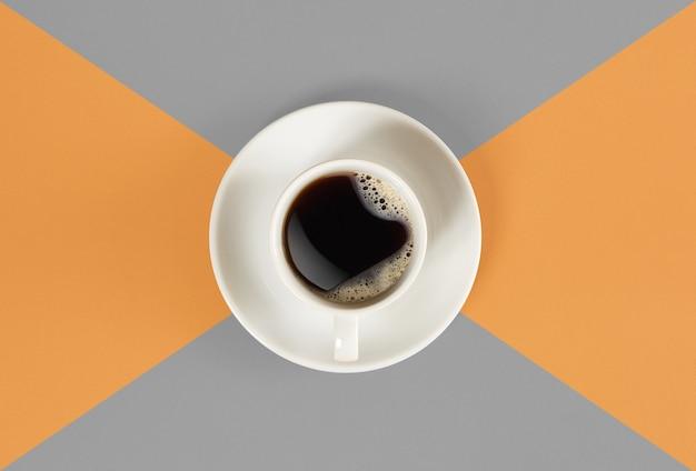 Une tasse de café noir sur fond orange et gris vue d'en haut