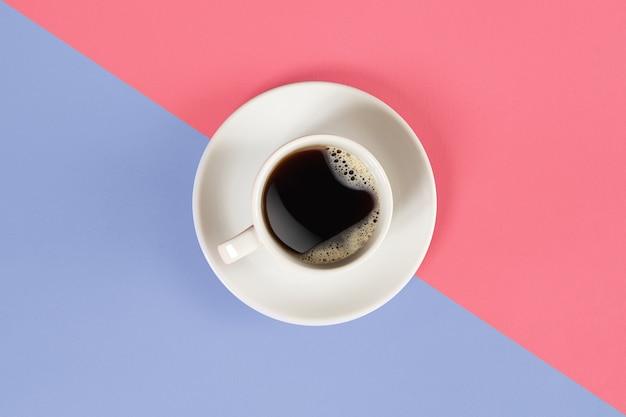Une tasse de café noir sur fond rose et lilas vue d'en haut