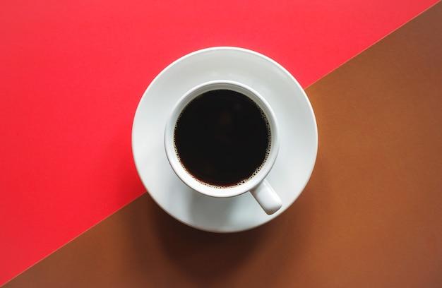 Tasse de café noir sur fond rouge et marron abstrait