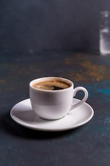 Tasse de café noir sur fond de tableau bleu
