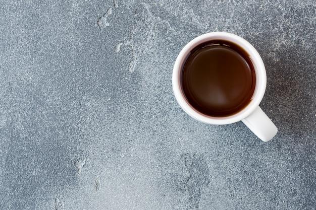 Tasse de café noir fort sur un béton. espace de copie