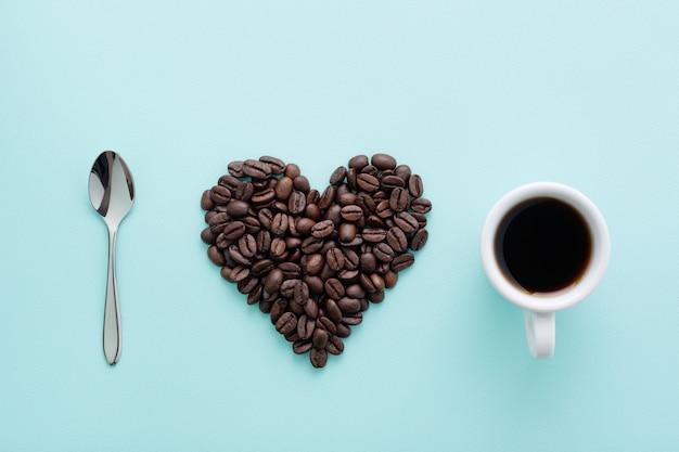 Tasse de café noir et grains de café sur fond bleu