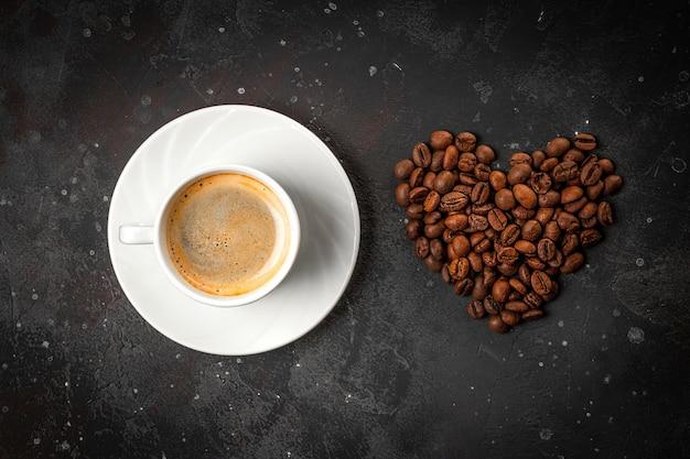 Une tasse de café noir et de grains de café en forme de coeur sur fond gris foncé