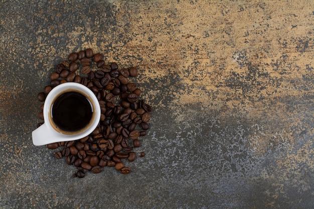 Tasse de café noir avec des grains de café sur une surface en marbre.