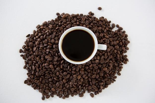 Tasse de café noir avec des grains de café torréfiés