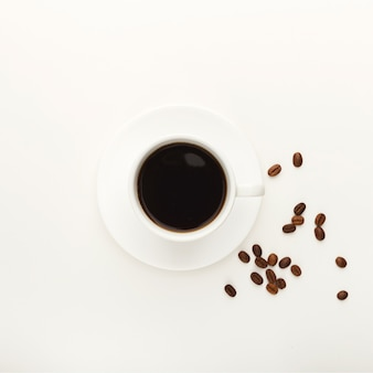Tasse de café noir et grains torréfiés sur fond isolé blanc. vue de dessus sur la boisson vivifiante. maquette pour la conception d'annonces, espace de copie