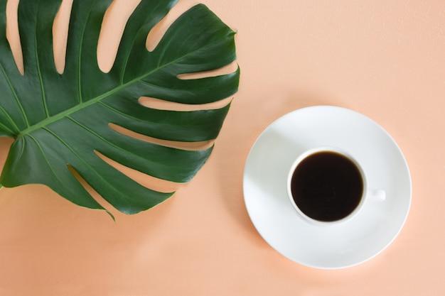 Tasse de café noir et de grandes feuilles vertes plante monstera sur rose