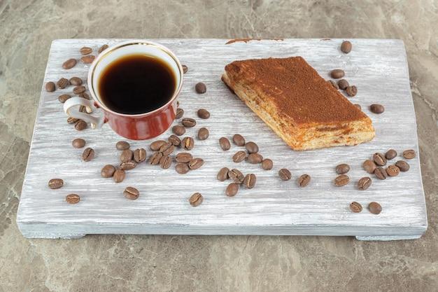 Tasse de café noir avec des haricots et des pâtisseries sur planche de bois