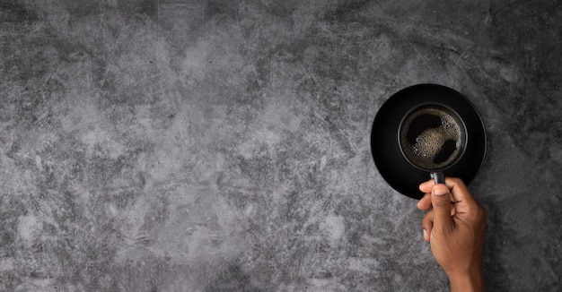 Tasse à café noir main humaine avec fond sur fond de texture mur grunge ciment avec espace copie à gauche.