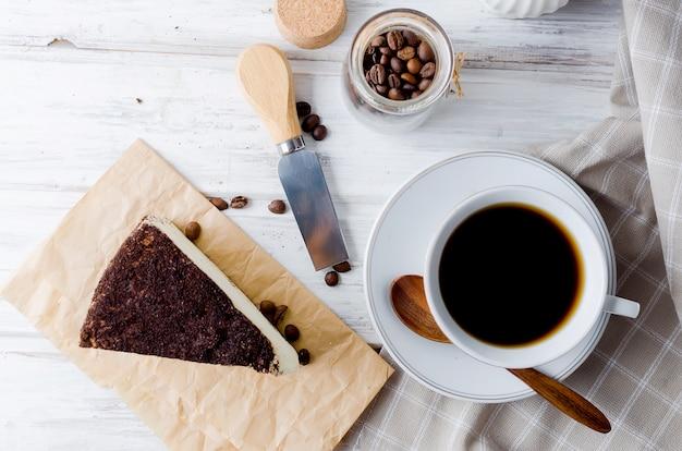 Tasse de café noir avec un morceau de fromage à pâte molle dans le café moulu