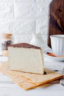 Tasse de café noir avec un morceau de fromage à pâte molle