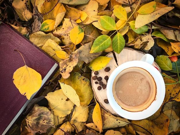 Tasse de café noir parmi le feuillage d'automne tombé