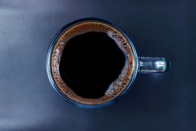 Tasse de café noir sur une plaque brune. boisson chaude préférée