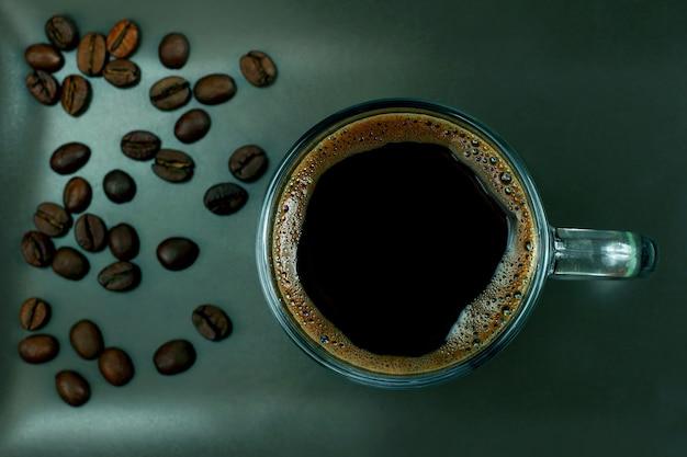 Tasse de café noir sur une plaque brune avec des grains de café. boisson chaude