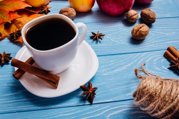 Une tasse de café noir sur une surface bleue