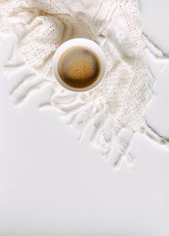Tasse de café noir sur table blanche avec une couverture au crochet