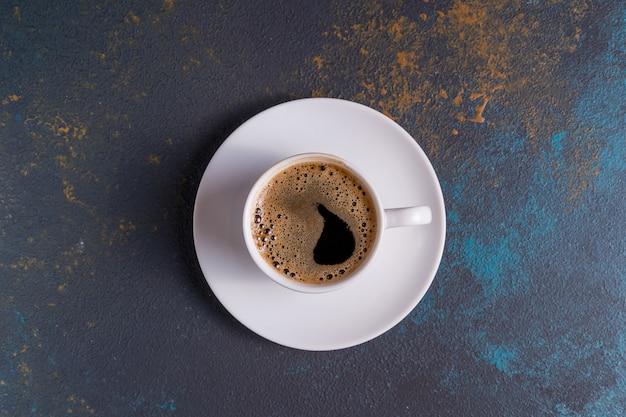 Une tasse de café noir sur table bleue, vue de dessus.