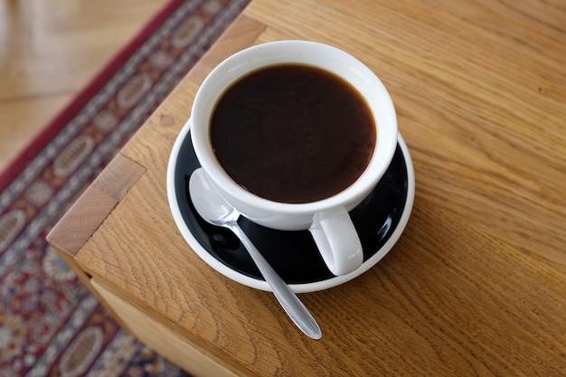 Tasse de café noir sur une table en bois, café du matin.