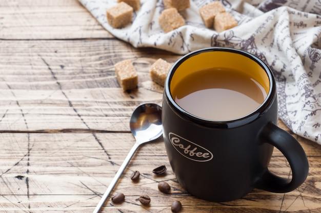 Tasse de café noir à la vapeur chaude avec des cubes de sucre sur une table en bois