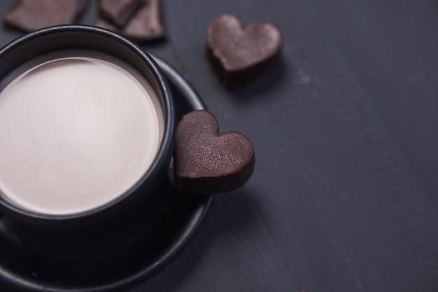 Tasse à café noire et biscuits au chocolat en forme de coeur sur fond sombre. mise au point sélective. copier l'espace