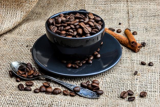 Tasse à café noire pleine de grains de café bio et de bâtons de cannelle sur toile de lin