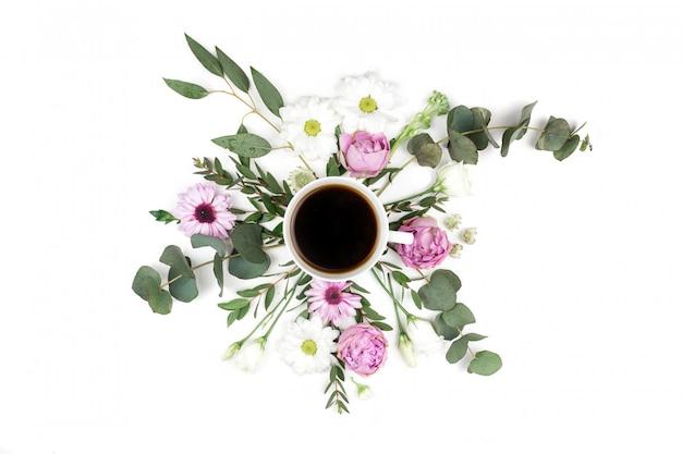 Tasse à café noire, roses roses et bouquet blanc de fleurs de chrysanthème et d'eucalyptus. mise à plat, vue de dessus