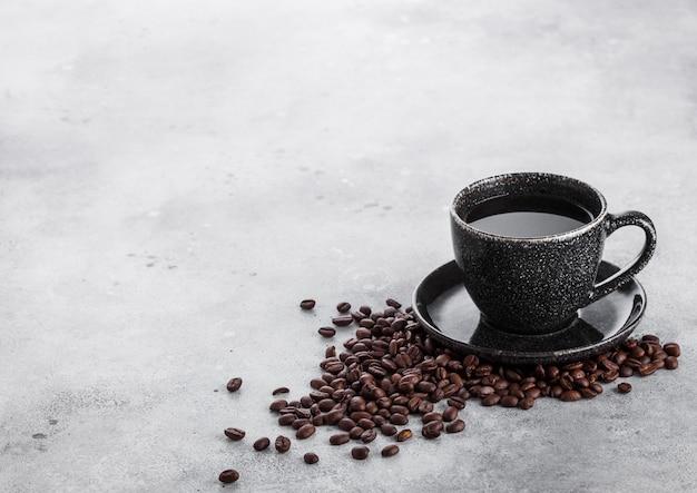 Tasse à café noire avec soucoupe et grains de café frais sur la table de cuisine en pierre.