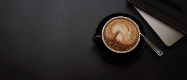 Tasse de café noire sur une table de travail sombre avec ordinateur portable, agenda et espace de copie