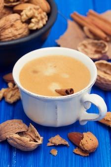 Une tasse de café et de noix sur une surface en bois