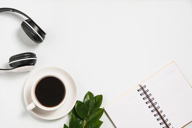 Une tasse de café avec note et casque sur un bureau blanc avec espace de copie.