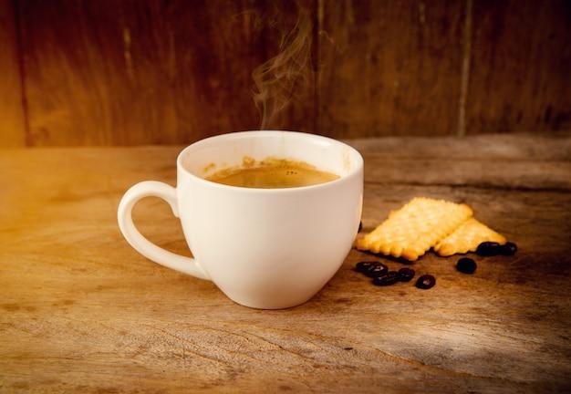 Tasse à café avec de la nourriture craquelée sur fond de bois