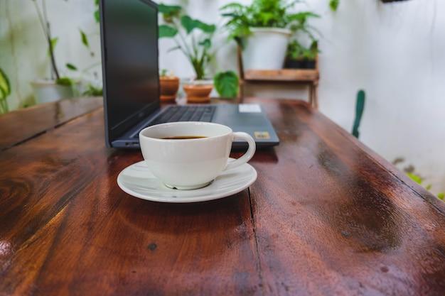 Tasse à café et ordinateur portable sur une table en bois dans le jardin