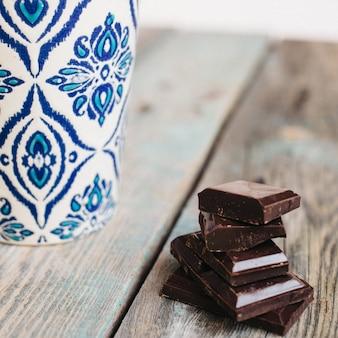 Tasse de café avec ornement bleu et chocolat sur une table en bois