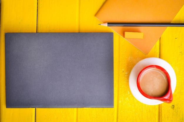 Tasse de café et de papeterie sur fond jaune